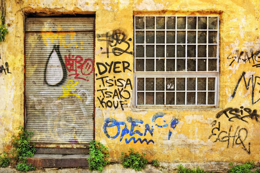 An old rusted roller door, covered in graffiti