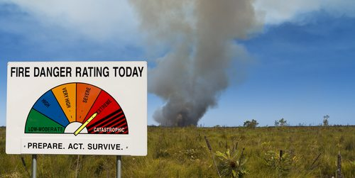 Fire danger rating board with smoke in the distance